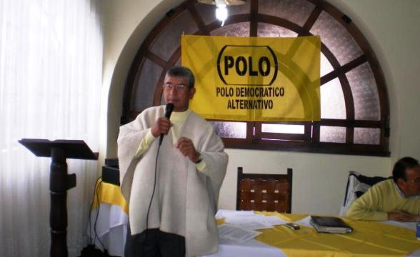 El sacerdote Gustavo Suárez Niño ofreciendo una misa en Chiquinquirá, con las banderas del comunista Polo Democrático detrás