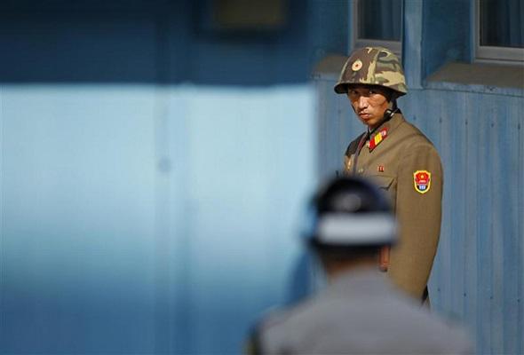 Soldado norcoreano mira como un soldado surcoreano presta guardia antes de la llegada de Juan Manuel Santos a Panmunjom, en la zona desmilitarizada que separa las dos Coreas, Paju y Seul (sep 14 de 2011)