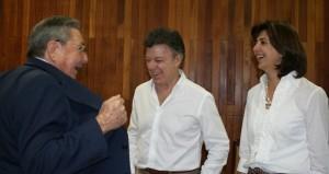 Juan Manuel Santos y la canciller maría Ángela Holguín ríen a carcajadas por lo que les enseña Raúl Castro