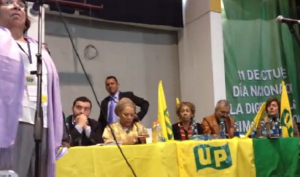 """Andrés Villamizar Pachón, director de la Unidad Nacional de Protección, ovacionando a Aida Avella en una reunión política de la UP en noviembre de 2013, y pidiendo un """"frente común contra los enemigos de la paz"""""""